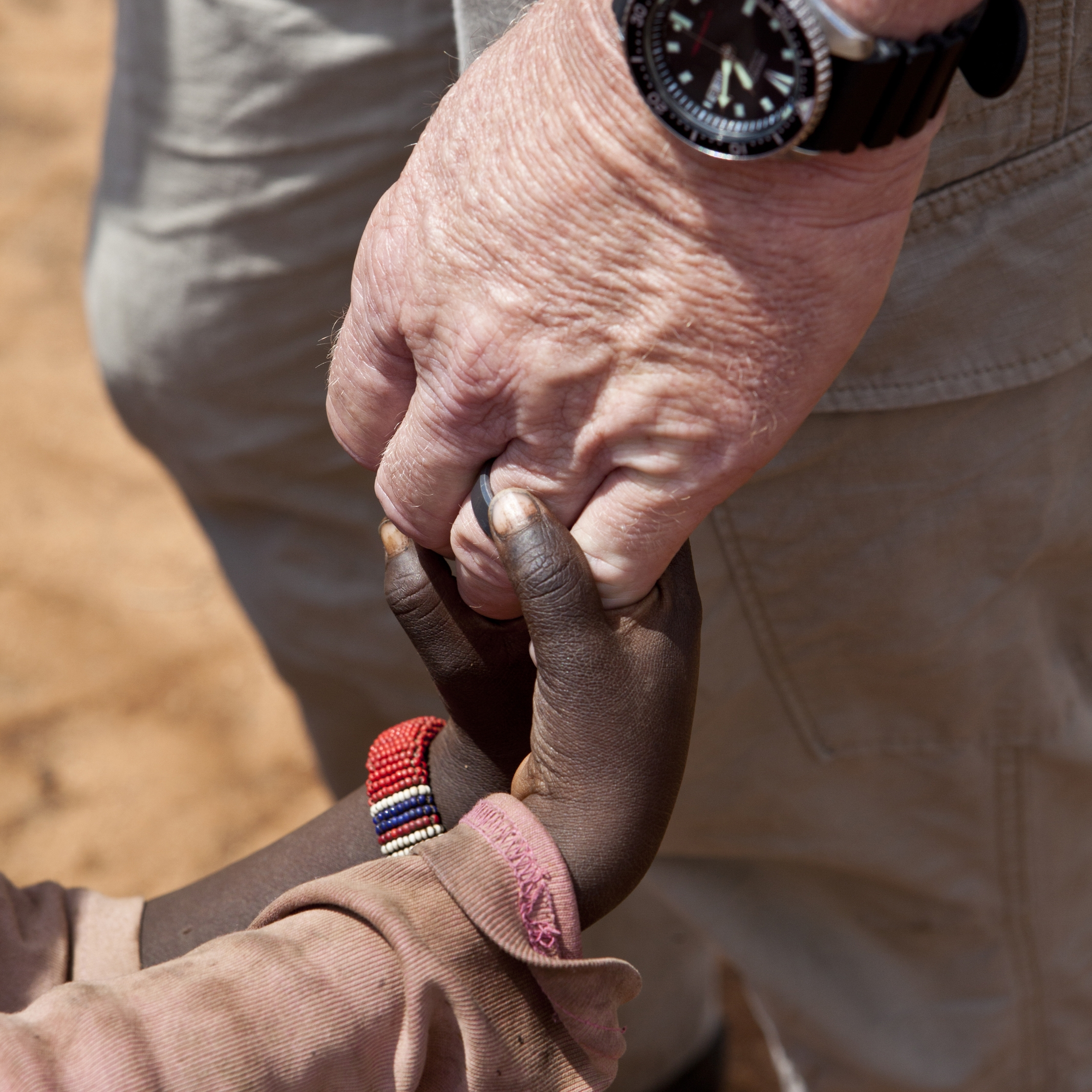 aid-workers-hands-holding-childrens-hands-PZVDV7U.jpg