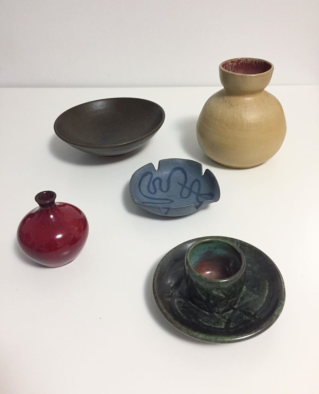"""5 pieces of lorenzen pottery - each piece sold separatelyDemi tasse - plate 5"""" diameter, entire height 2""""Shallow brown bowl - 7"""" diameter, 2"""" heightBlue dish - 4.75"""" length, 4.5"""" width, 1"""" heightRed vase - 3.25"""" height, 3"""" diameter, comes in original Lorenzen boxYellow vase - 5.5"""" height x 5"""" width"""