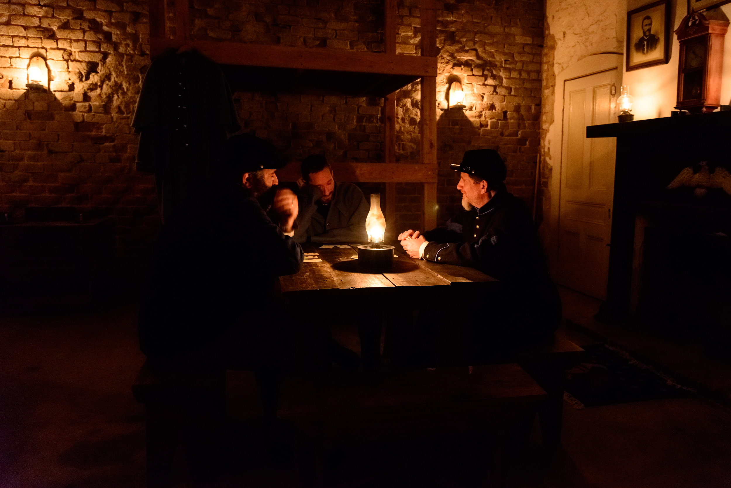 Volunteer re-enactors staying in the fort over night play cards to pass the time.