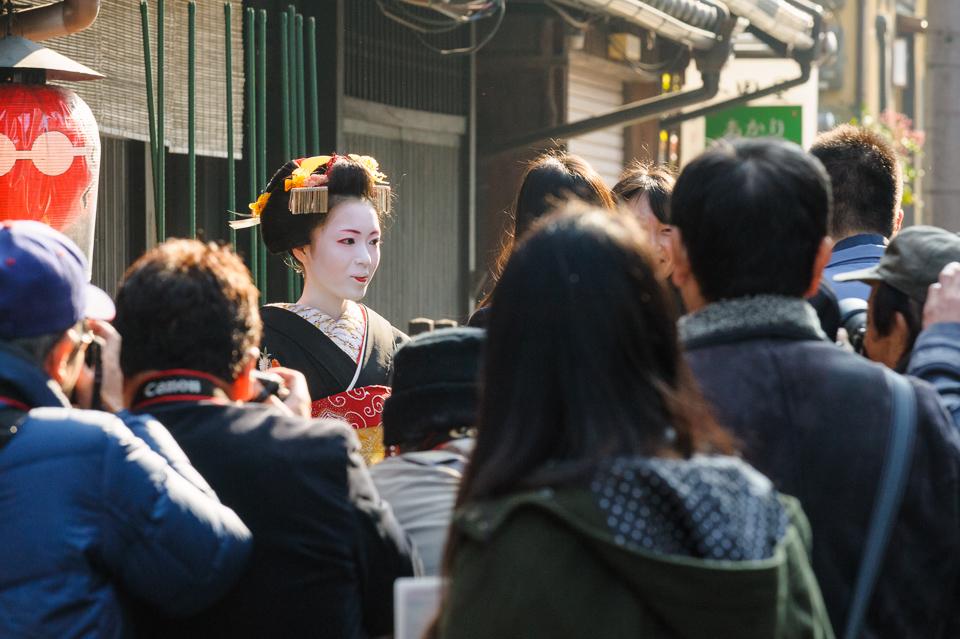 Photographers surround the maiko Katsusen of Gion Kobu during her omisedashi on December 5, 2013