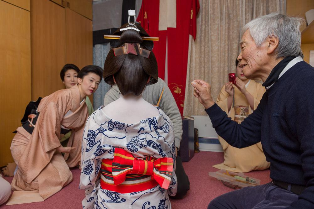 Veteran geisha Momicho checks the wig of new geisha Momifukku