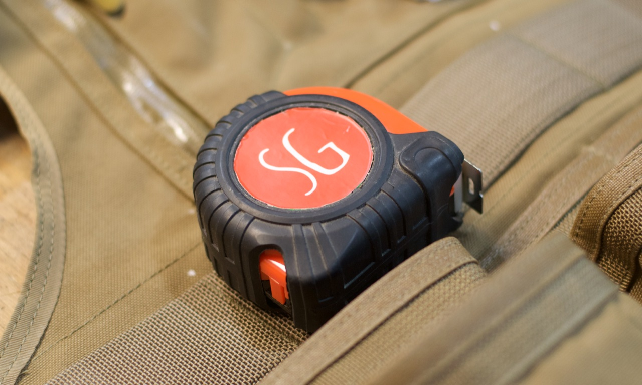 Clamp your tape measure to any of the webbing places on the vest