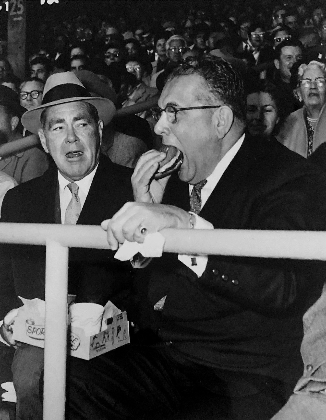 Arthur, chomping a hamburger, in the stands at the Chicago Stadium with partner Jimmy Norris.