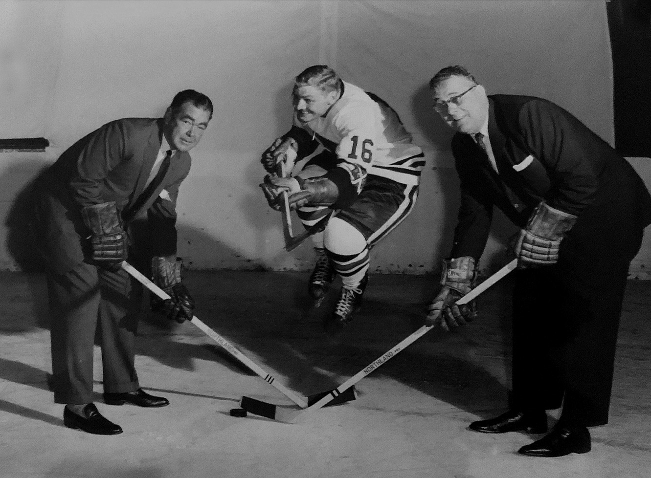 Arthur ( right ) with partner Jimmy Norris. In between them, superstar player Bobby Hull clowns around in his original number 16 jersey from his first few years with the Blackhawks (1957 to 1961). Hull later switched to number 7 and again to the now-retired number 9 as a tribute to his idol Gordie Howe.