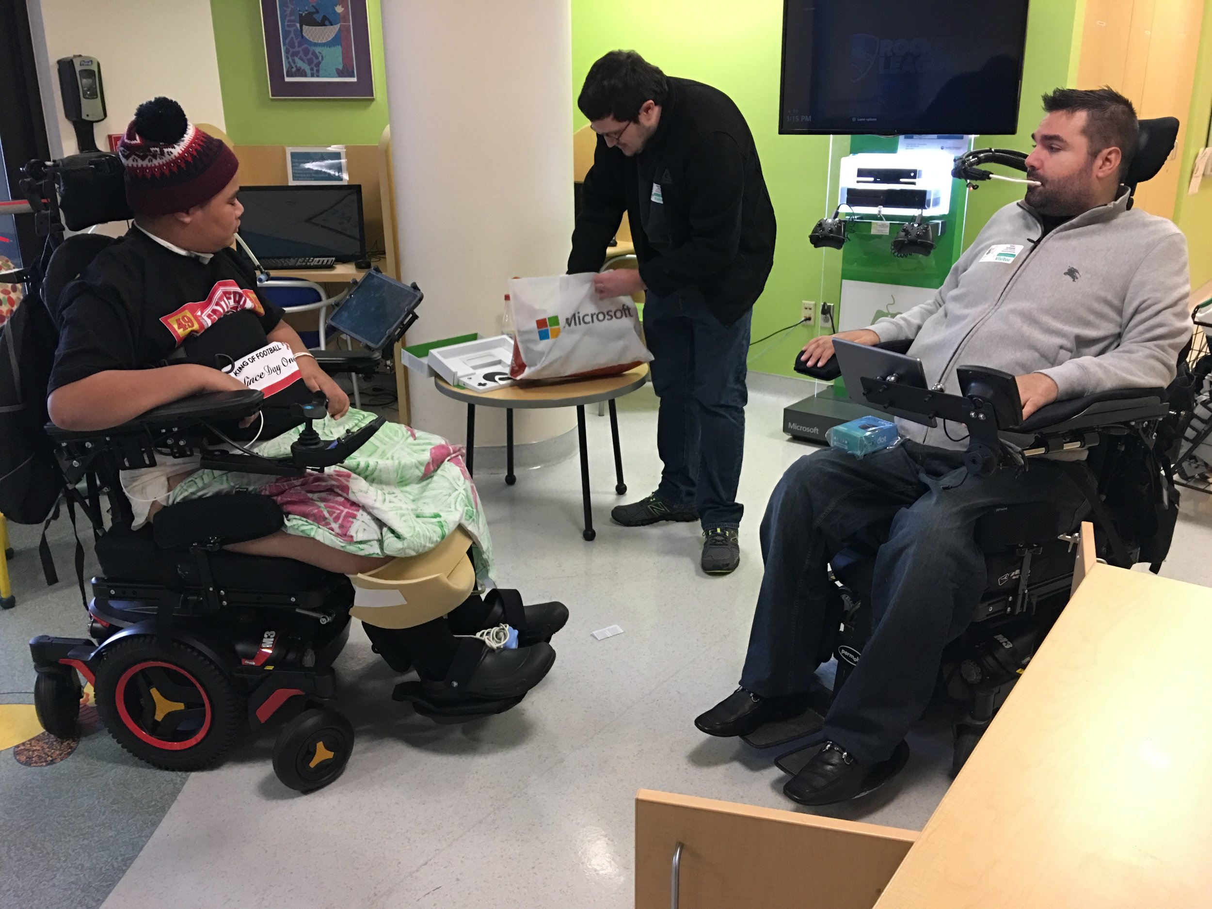Maui (Pictured on Left) at Seattle Children's Hospital receiving a Microsoft adaptive controller from Tyler (Pictured on right) and the TSF.