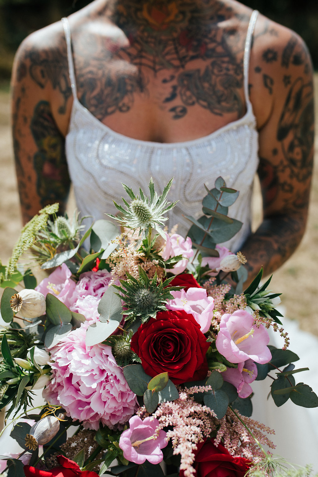 Tattooed bride with red and pink hand-tied bouquet