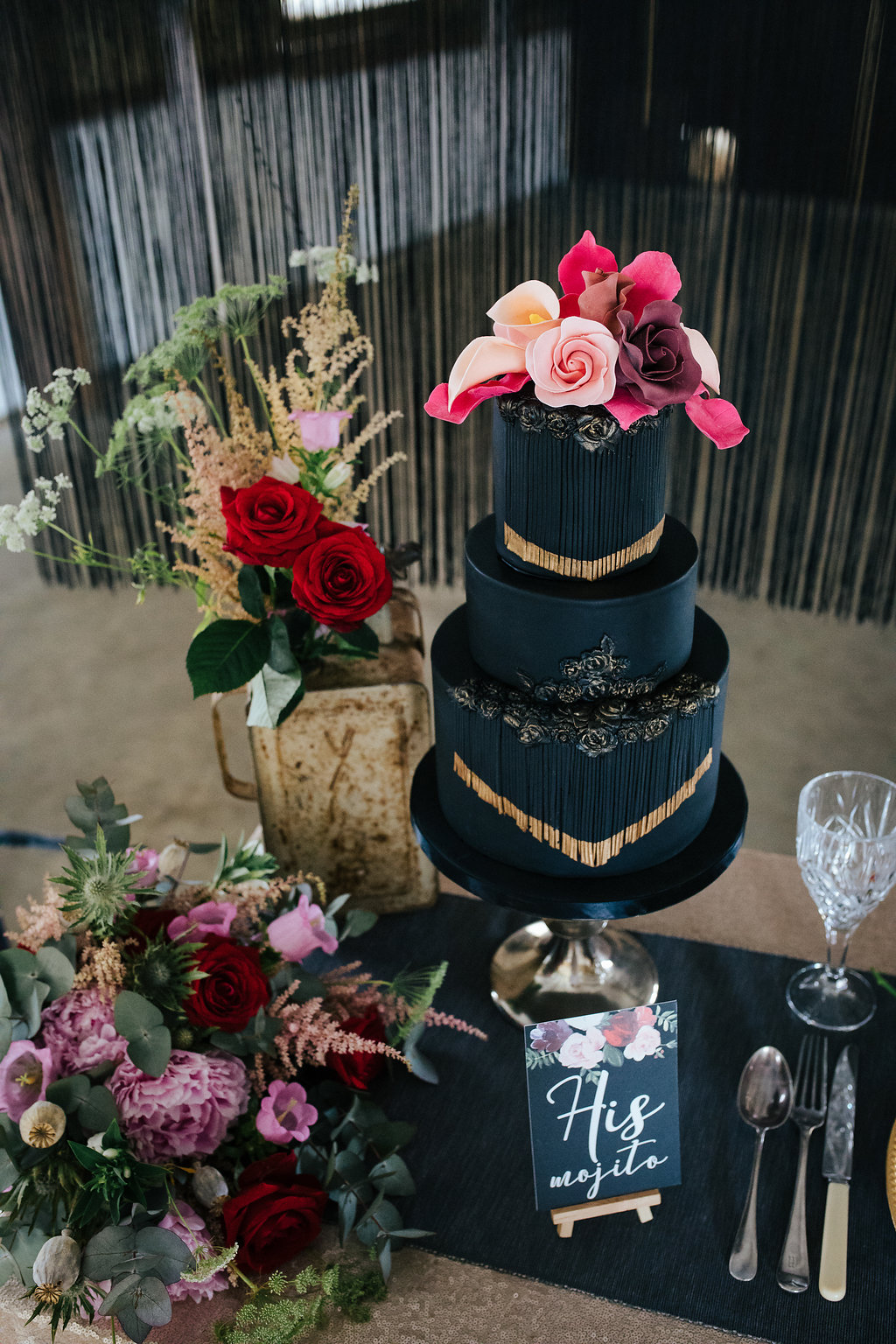 Black tasselled wedding cake with sugar flowers