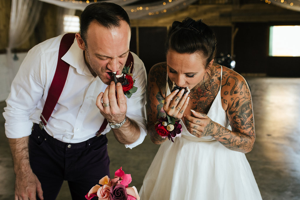 Tattooed bride and groom eating wedding cake