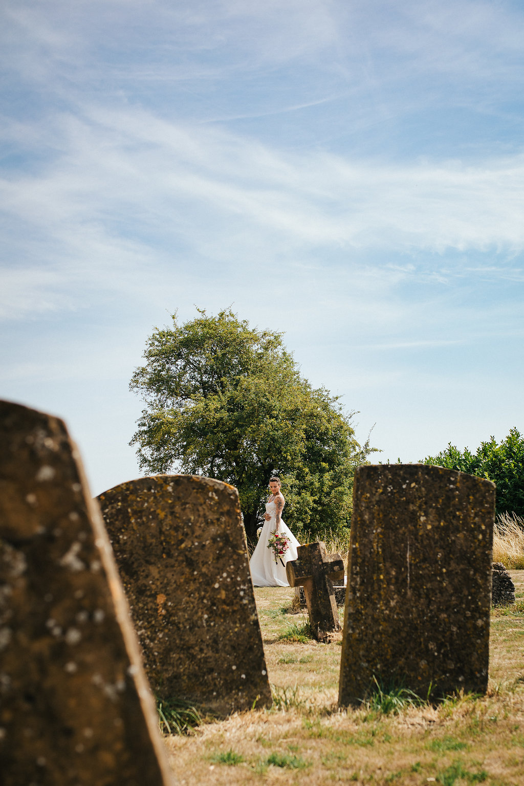 Tattooed bride walking in the churchyard
