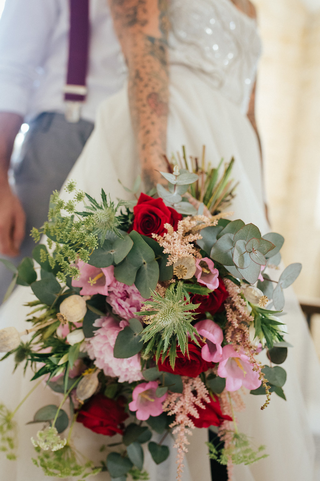 Hand-tied wedding bouquet in red and pink with foliage