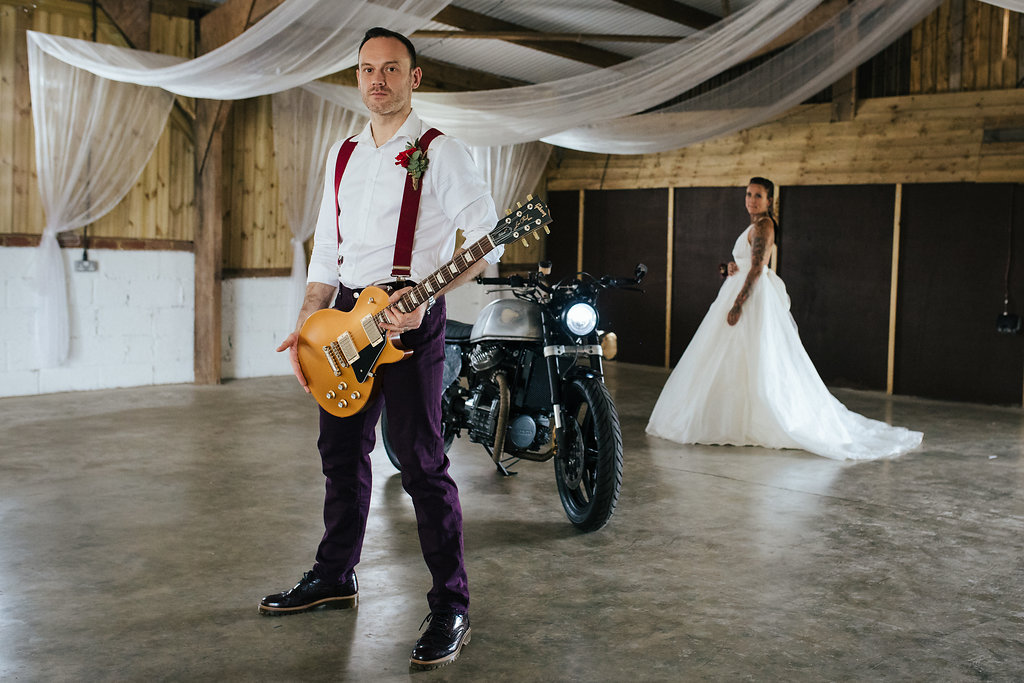 Rock n' roll bride and groom with guitar and vintage motorbike