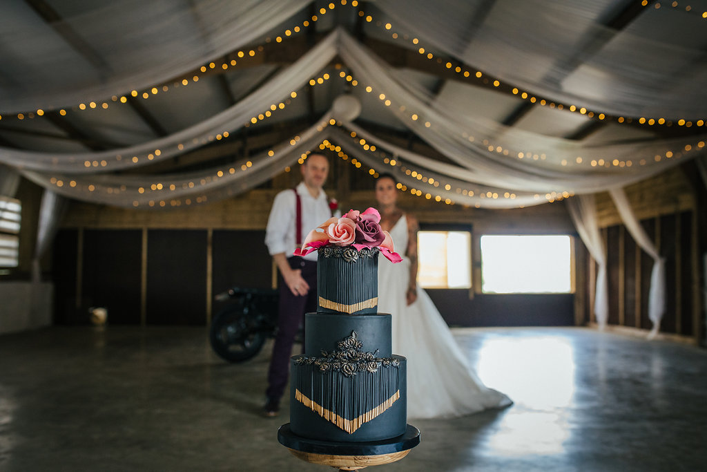 Black wedding cake with tassels and red and pink sugar flowers