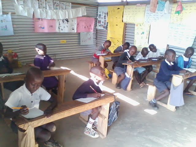 Children sitting and learning in a classroom at Captain Silvery Academy.