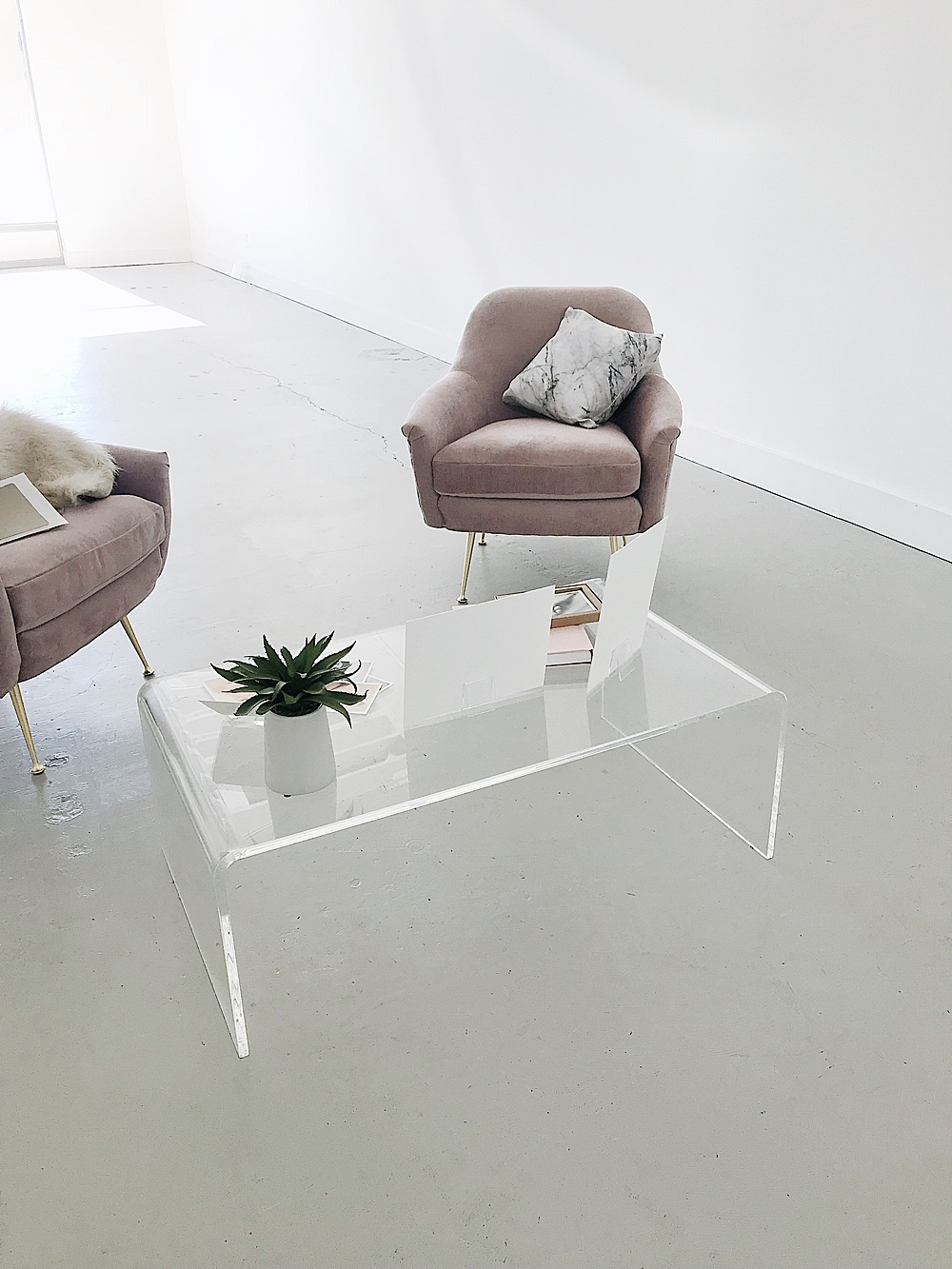 chic white room with beige chairs clear coffee table