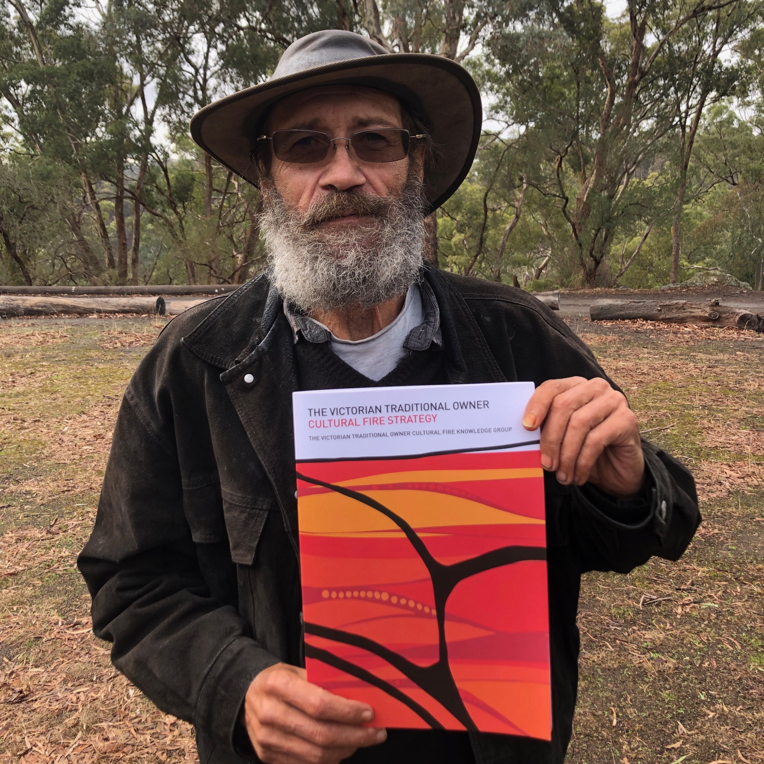 Wurundjeri Elder Dave Wandin with a copy of the Victorian Traditional Owner Cultural Fire Strategy.
