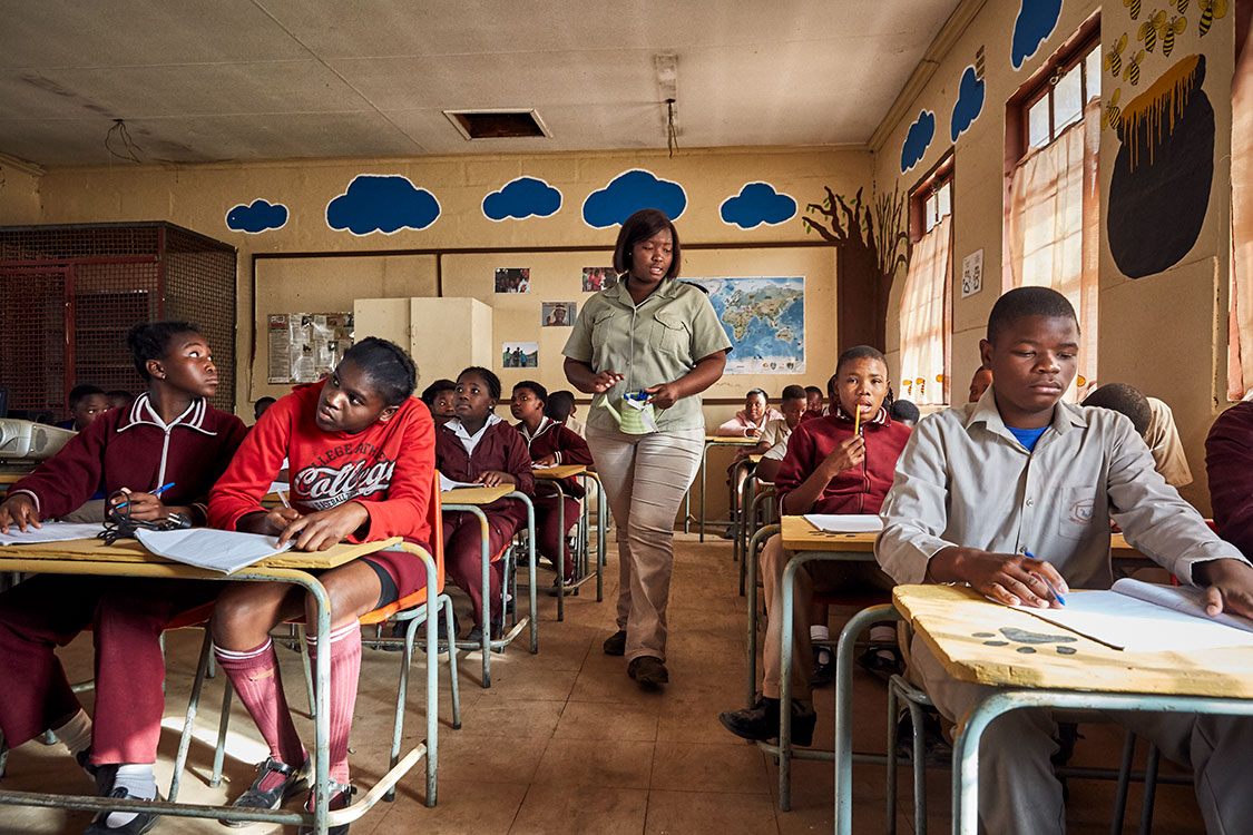 Bush Babies education officer Lewyn Maefala hands out pens to those students who do not own one, Mhala Mhala Primary School, South Africa, 2017.   Due to a lack of resources like stationary, Lewyn has to collect the pens she hands out to students in order to be able to re-use them at the next school.