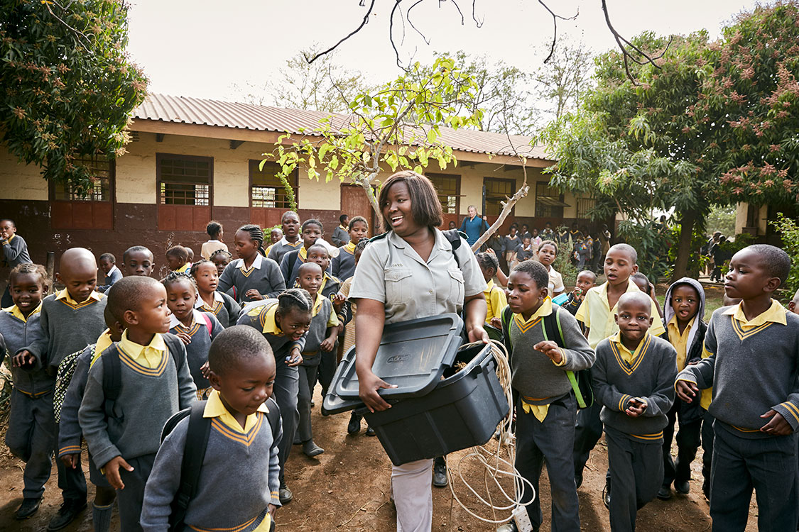 Students at Phalaborwa Primary School crowd around Bush Babies education officer Lewyn Maefala who carries a plastic box filled with elephant dung, South Africa, 2017.   In the background, Herman, a Norwegian volunteer, carries Lewyn's projection screen. Most days, however, she is on her own.