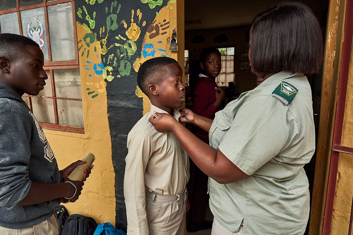 Every student's attendance record and appearance are checked before class starts, Mhala Mhala Primary School, South Africa, 2017.