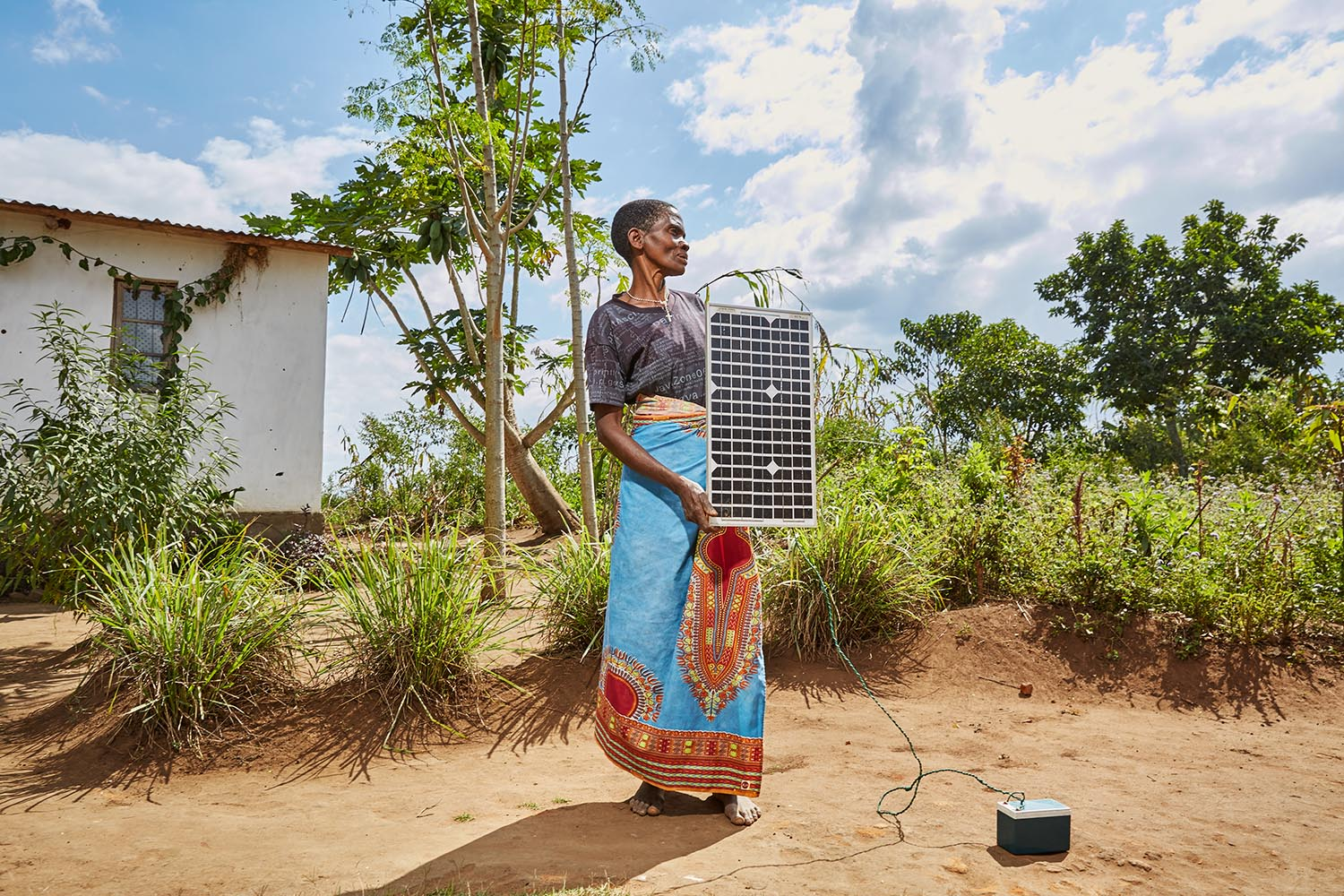 Violet Napazi, 57, holds up the solar panel owned by her son, Master, Luchenza, southern Malawi, 2017.  Charging mobile phones is becoming a profitable business, especially since solar panels are becoming cheaper to buy and build. Until recently, Violet's family used the solar panel to charge a battery which was then to used charge mobile phones. But since the inverter burnt out, it can only power one phone at a time.