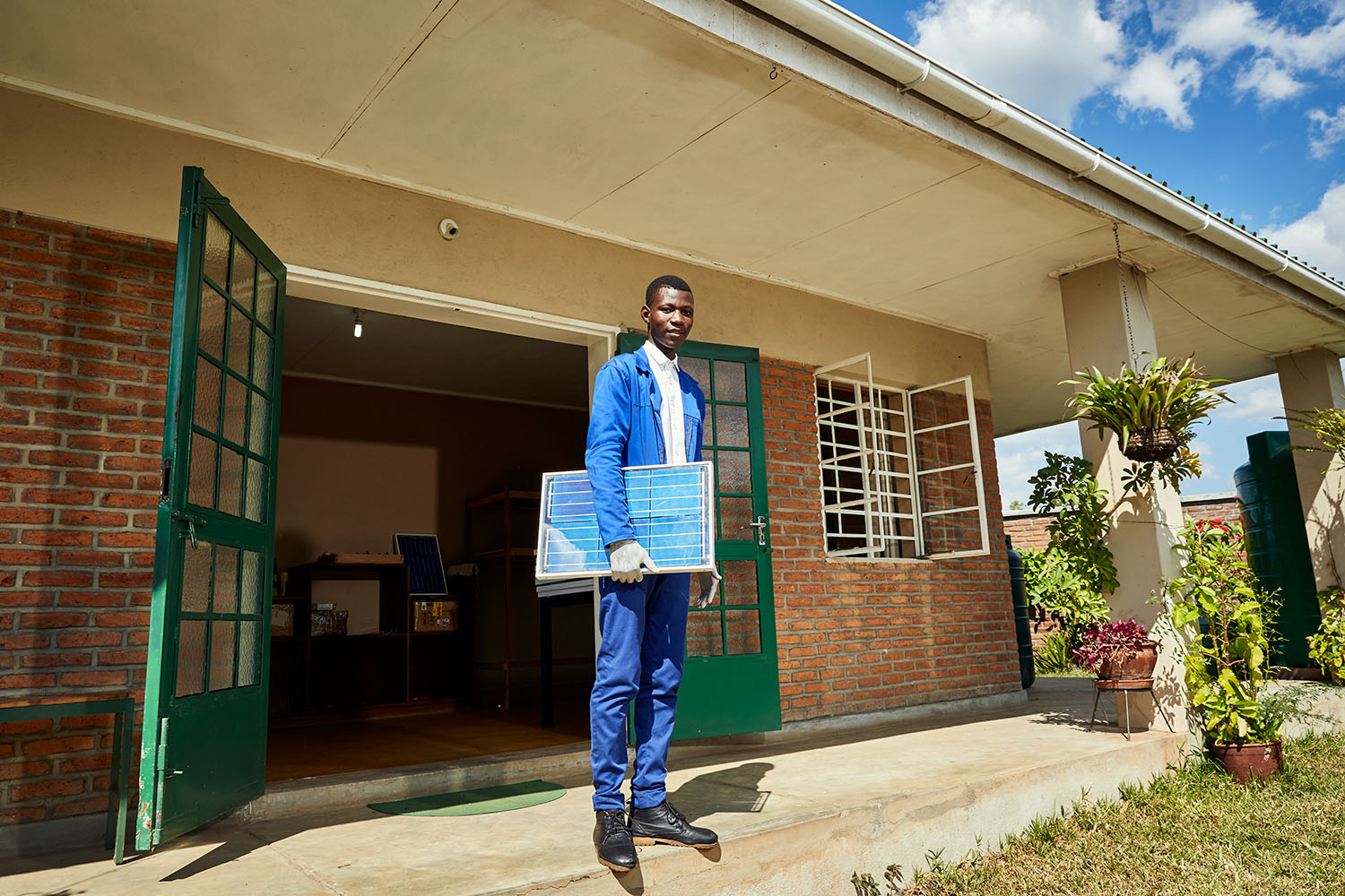 Thomas, a student at Green Malata, an entrepreneurial village, pose with a solar panel, Luchenza, southern Malawi, 2017.  Thomas and his fellow students are part of Green Malata's Renewable Energy course, during which they learn about a range of different green alternatives to on-grid electricity generation.
