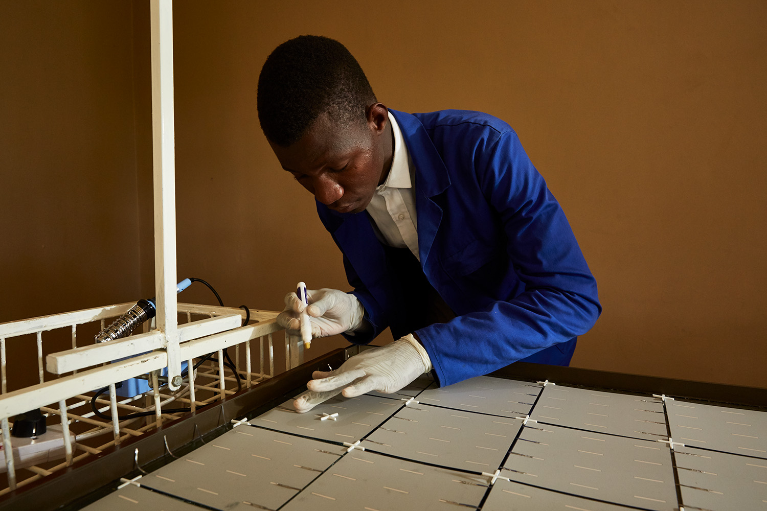 Thomas, a student at Green Malata, an entrepreneurial village, carefully solders metal strips to the back of a solar panel, Luchenza, southern Malawi, 2017.  Thomas and his fellow students are part of Green Malata's Renewable Energy course, during which they learn about a range of different green alternatives to on-grid electricity generation.