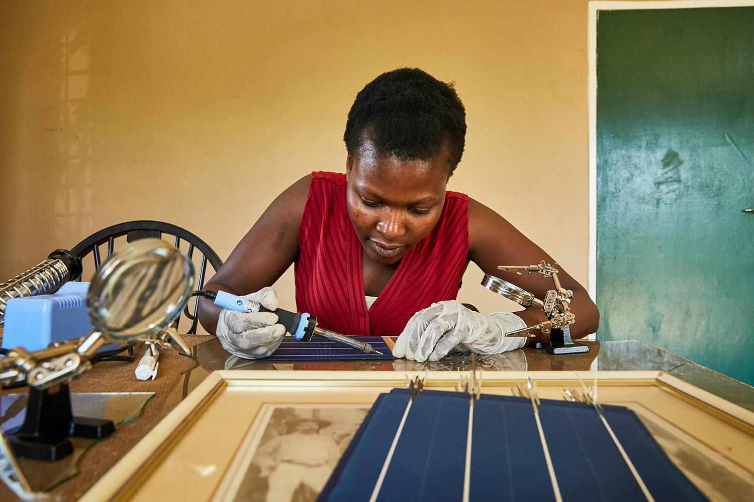 Jennifer, student at Green Malata, learn how to assemble solar panels, Luchenza, southern Malawi, 2017.  Green Malata teaches a variety of renewable energy skills, including solar panel building and maintenance, biogas generation, and wind turbines. As solar panel technology becomes cheaper and easier to use, training villages like Green Malata can afford to not only use them as part of their curriculum, but also to sell and rent them out to local villagers, providing much needed extra income.