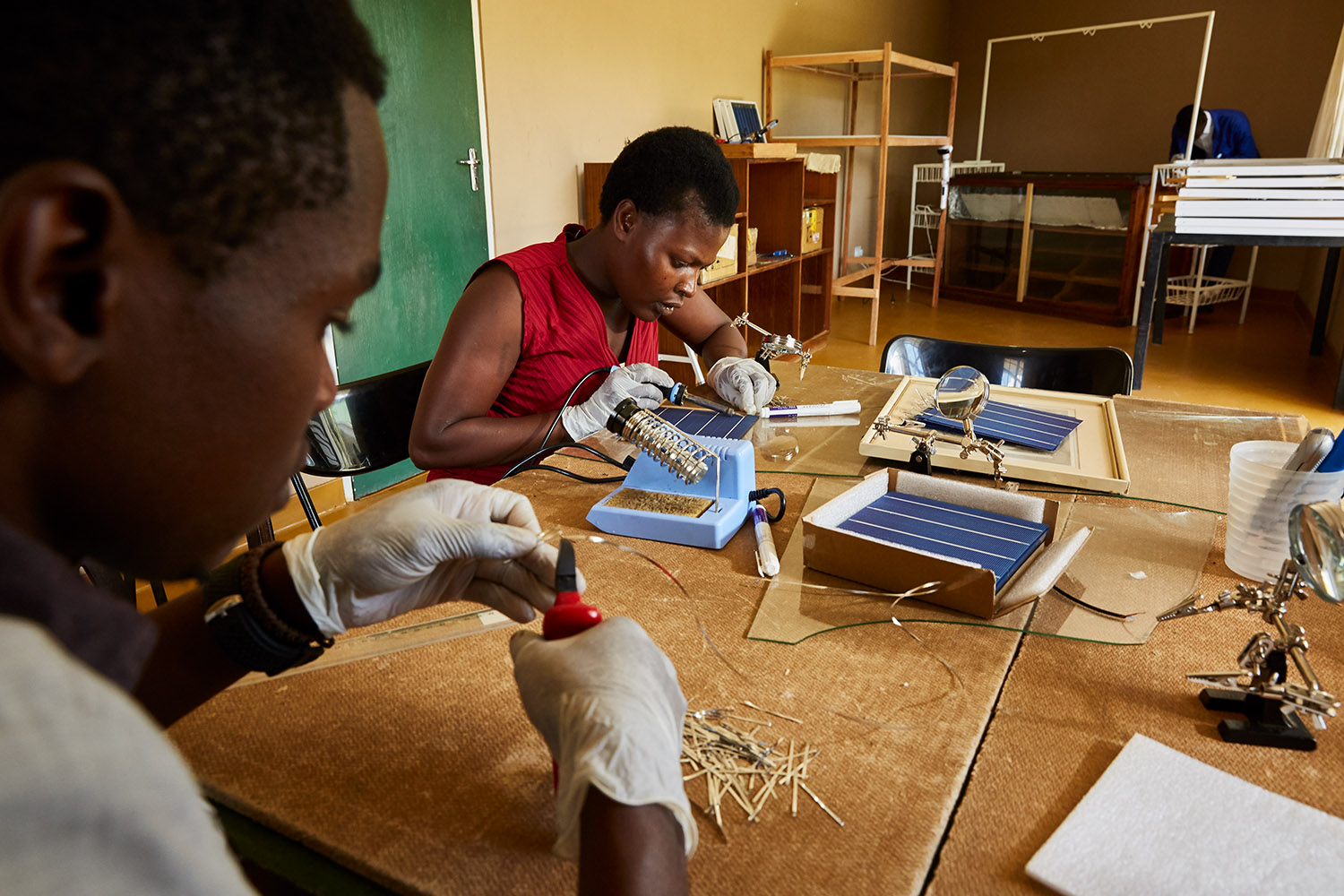 Alex and Jennifer, students at Green Malata, learn how to assemble solar panels, Luchenza, southern Malawi, 2017.  Green Malata teaches a variety of renewable energy skills, including solar panel building and maintenance, biogas generation, and wind turbines. As solar panel technology becomes cheaper and easier to use, training villages like Green Malata can afford to not only use them as part of their curriculum, but also to sell and rent them out to local villagers, providing much needed extra income.
