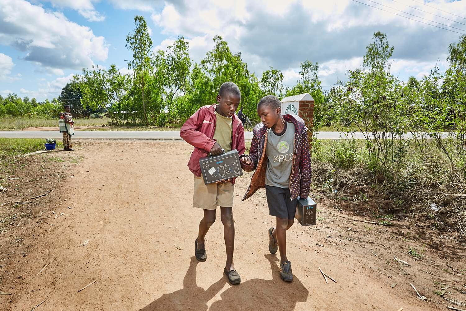 From left to right: Jan Chumba (12) and his brother Ben (10) carry two solar batteries home, after picking them up at Green Malata, an entrepreneurial training village that offers a variety of green alternatives to Malawi's notoriously unreliable national electricity provider, ESCOM, Luchenza, southern Malawi, 2017.