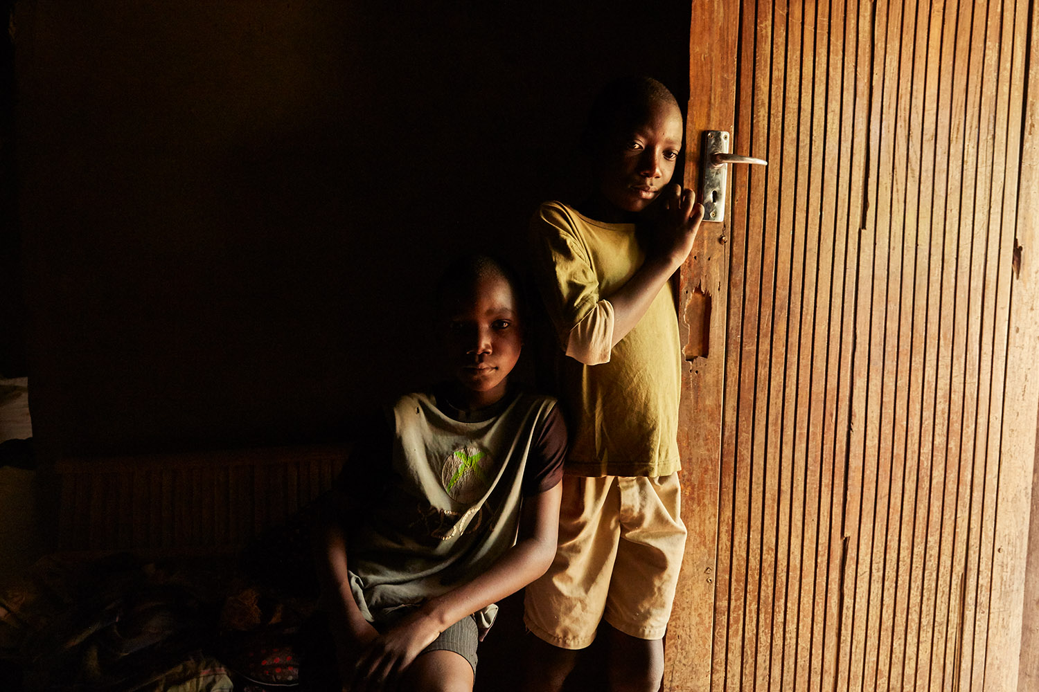 Jan Chumba (12) and his brother Ben (10) in the doorway of their home, Chiuta village, southern Malawi, 2017.  During the day, the only light inside comes from the open door and windows.