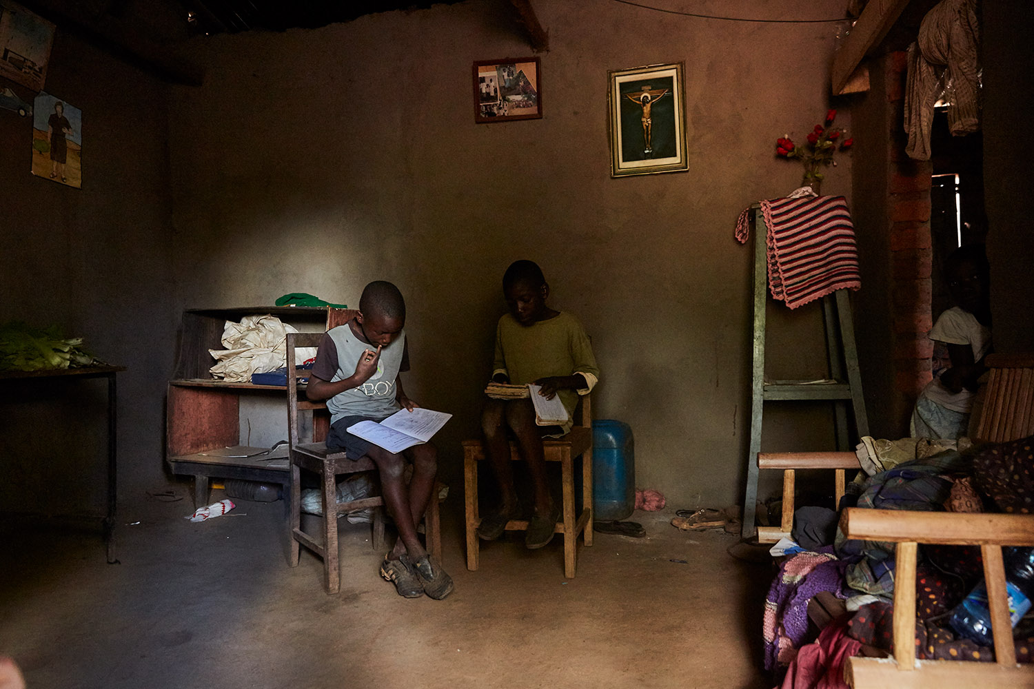 Jan Chumba (12) and his brother Ben (10) studying at home with the daylight that falls into their home, Luchenza, southern Malawi, 2017.