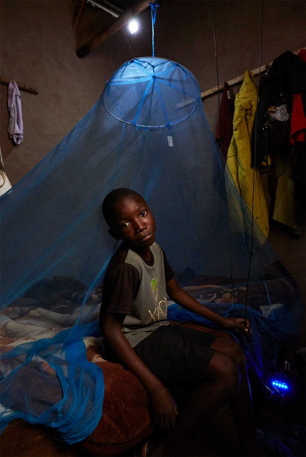 Ben Chumba (10) sits on his bed, lit by a light bulb which is powered by a solar battery, visible in the bottom right hand corner of the image, Chuita village, southern Malawi, 2017.