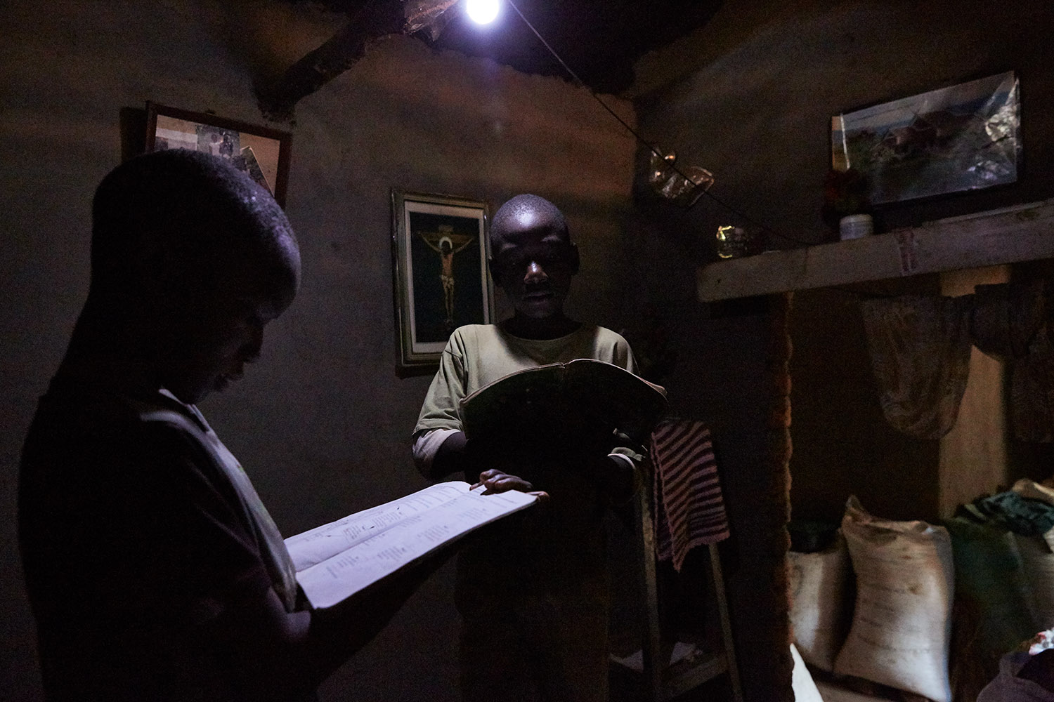 Jan Chumba (12) and his brother Ben (10) studying at home with the solar battery powered light, Luchenza, southern Malawi, 2017.