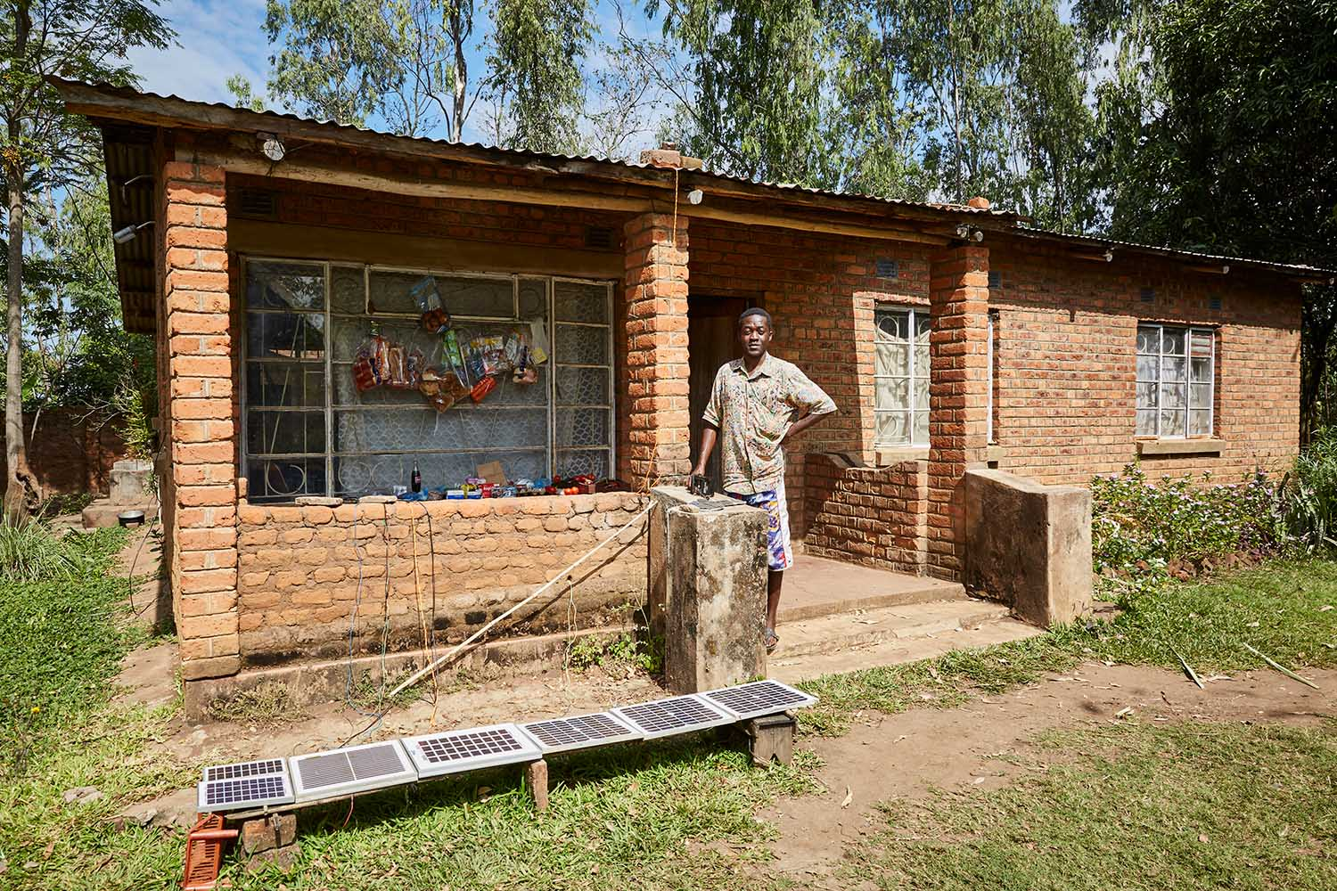 Felix Wonga (29) stands next to the small store he runs with his father, Robert (56), Luchenza, southern Malawi, 2017.  Felix runs the mobile phone charging business, while his father takes care of the shop front. The solar panels laid out in front of the store power a car battery which, Felix uses to charge up to five mobile phones at once. Because Felix and Robert's home is the only one in the area with solar panels, business is good.