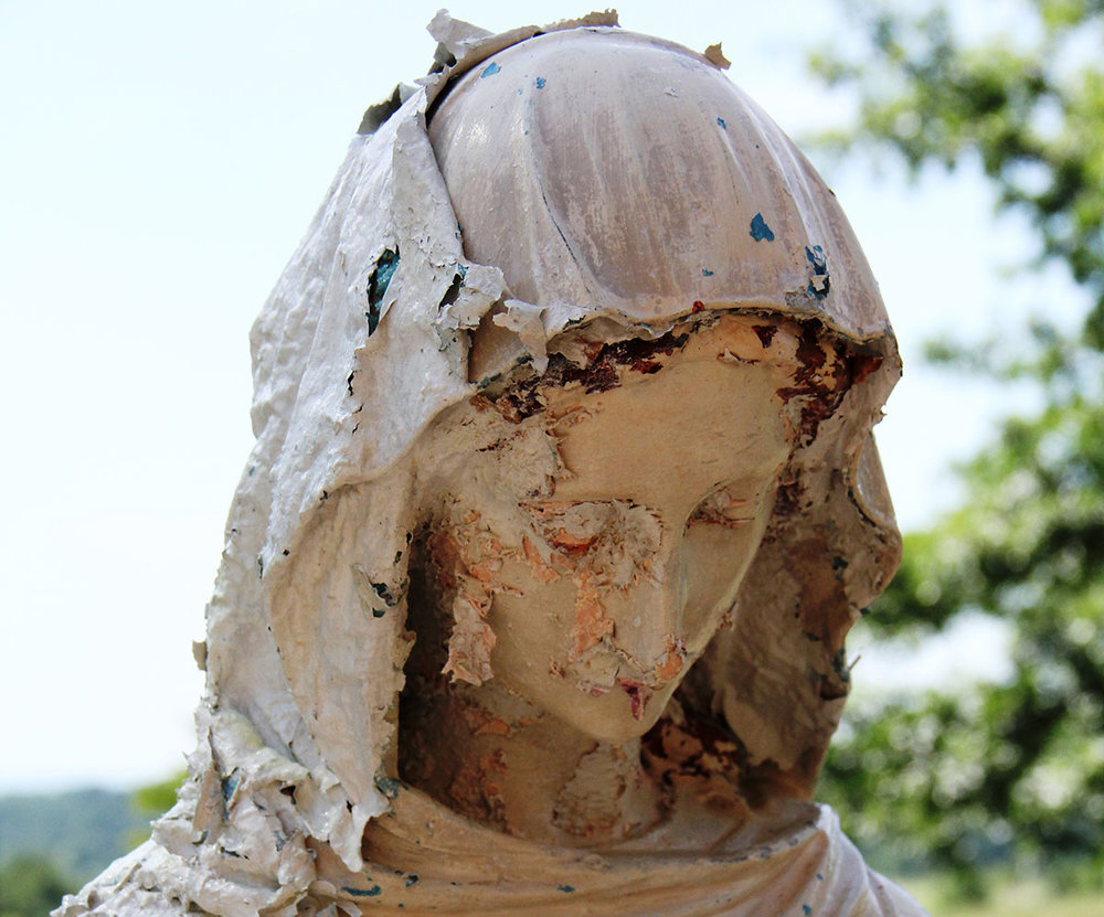 A marble sculpture covered with layers of flaking paint.