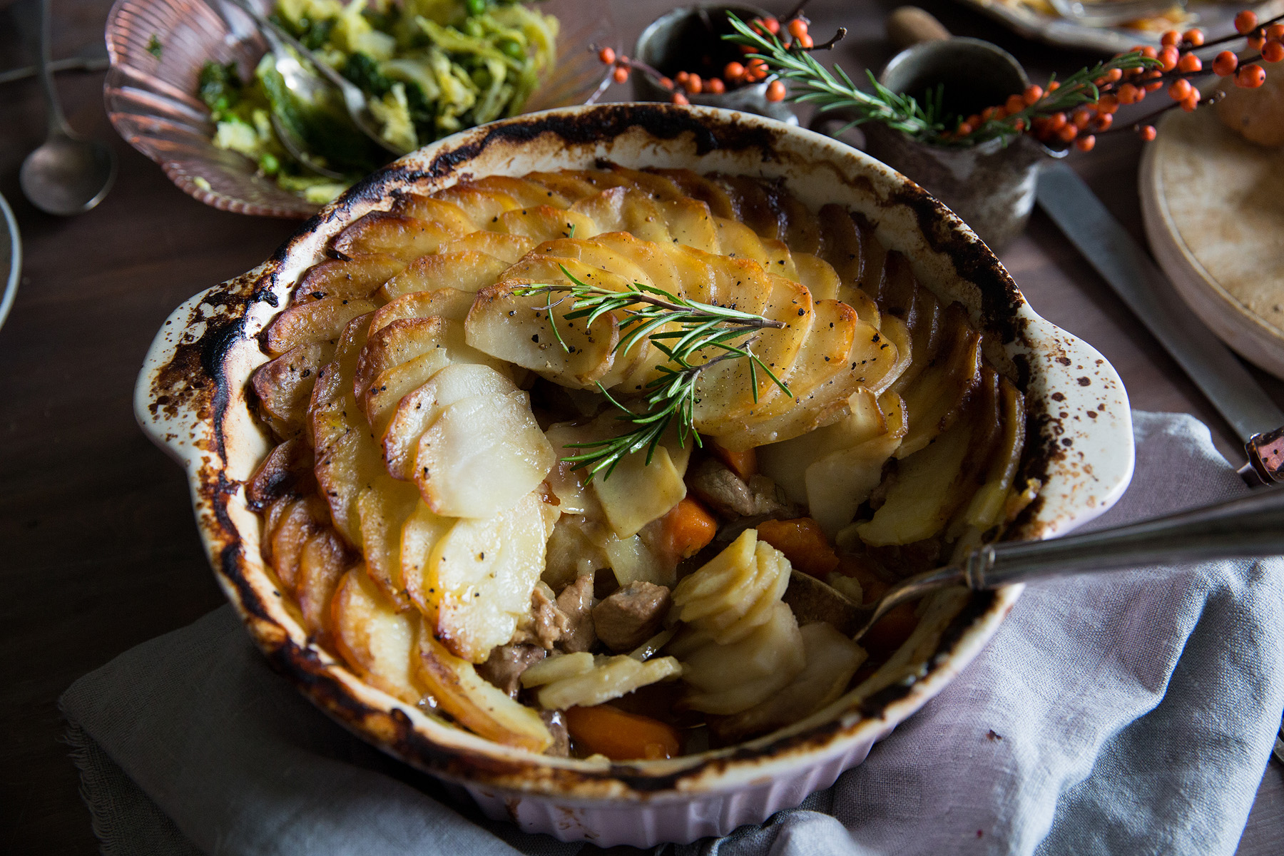 Lamb hotpot  A hearty casserole that deserves its place as a classic  Serves 6–8 2 tbsp plain flour 900g diced lamb 2 tbsp vegetable oil 2 large onions, sliced 1 large garlic bulb, cloves peeled and left whole 8 small shallots, peeled 500g Chantenay carrots, scrubbed 1 tbsp Dijon mustard 1 tsp chopped fresh rosemary, plus extra to garnish 500ml chicken or vegetable stock 750g Maris Piper potatoes, unpeeled, scrubbed and cut into 5mm slices 40g butter, melted  1 Tip the flour into a bowl, and season with a few pinches of sea salt and a good grinding of black pepper. Add the lamb and toss to coat in the flour. Heat half the oil in a large ovenproof casserole dish and add the lamb (you may need to do this in two batches). Cook for 5–6 mins, until brown all over, then transfer to a plate with a slotted spoon and set aside. 2 Add the remaining oil to the same casserole dish and gently fry the onions for around 5 mins, until translucent. Add the garlic cloves and cook for a further minute before adding the shallots and carrots. Cook, stirring, for a further 2–3 mins. 3 Return the lamb to the casserole dish, and add the mustard and chopped rosemary. Season and stir well, before stirring through the stock. 4 Preheat oven to 180C/Fan 160C/ 350F. Arrange the potato slices on top of the lamb, overlapping slightly to create a lid for the hotpot. Brush with the melted butter, season with salt and black pepper, and cover with a lid or foil. Bake for 11⁄2 hours. 5 Remove the lid or foil, turn up the oven to 200C/Fan 180C/400F, and cook for a further 30–40 mins, or until the potatoes are golden brown. Garnish with rosemary sprigs.  This recipe was created for  The Simple Things  magazine Nov 2017