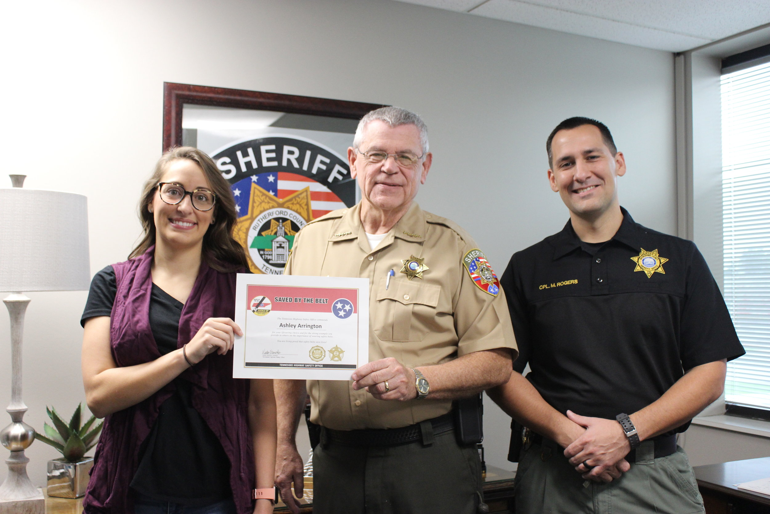 "Ashley Arrington receives a ""Saved by the Belt"" award from Sheriff Mike Fitzhugh and Cpl. Michael Rodgers. Arrington wore her seat belt when a vehicle crashed into her car and forced her into a semi-truck. She was not injured."