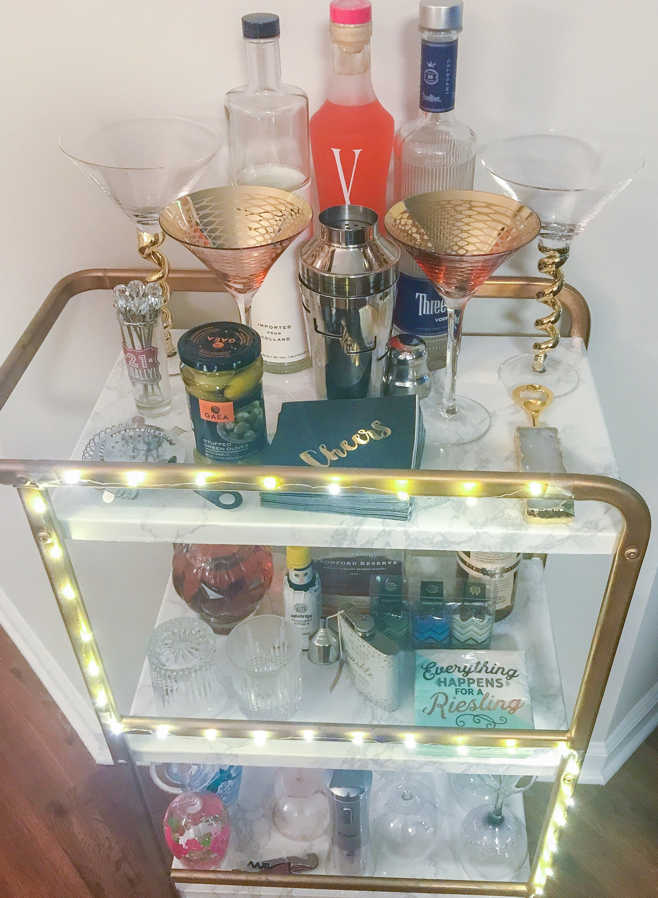 I made this bar cart and had it in my old apartment when I lived alone, and since Mack and I have moved in together he has made it his pride and joy (besides the fairy lights). I think it looks so cute the way he has it! Top shelf is liquor, middle shelf is bourbons, and the bottom shelf is a few of my most precious wine glasses on display.