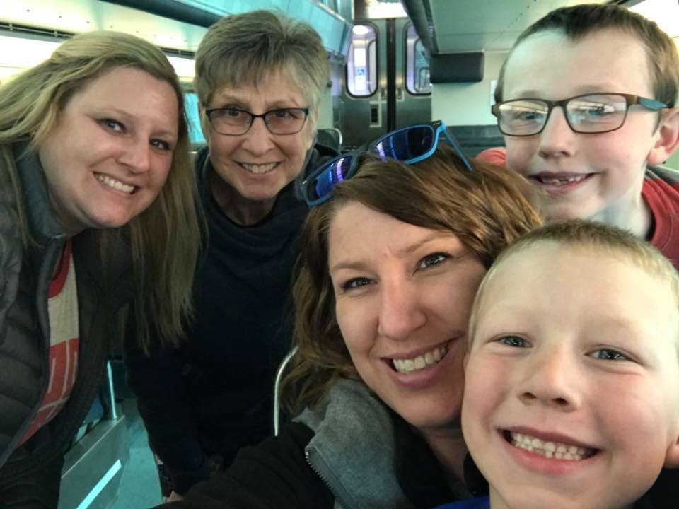 emily with her mom, sister and nephews on the train to the shedd aquarium