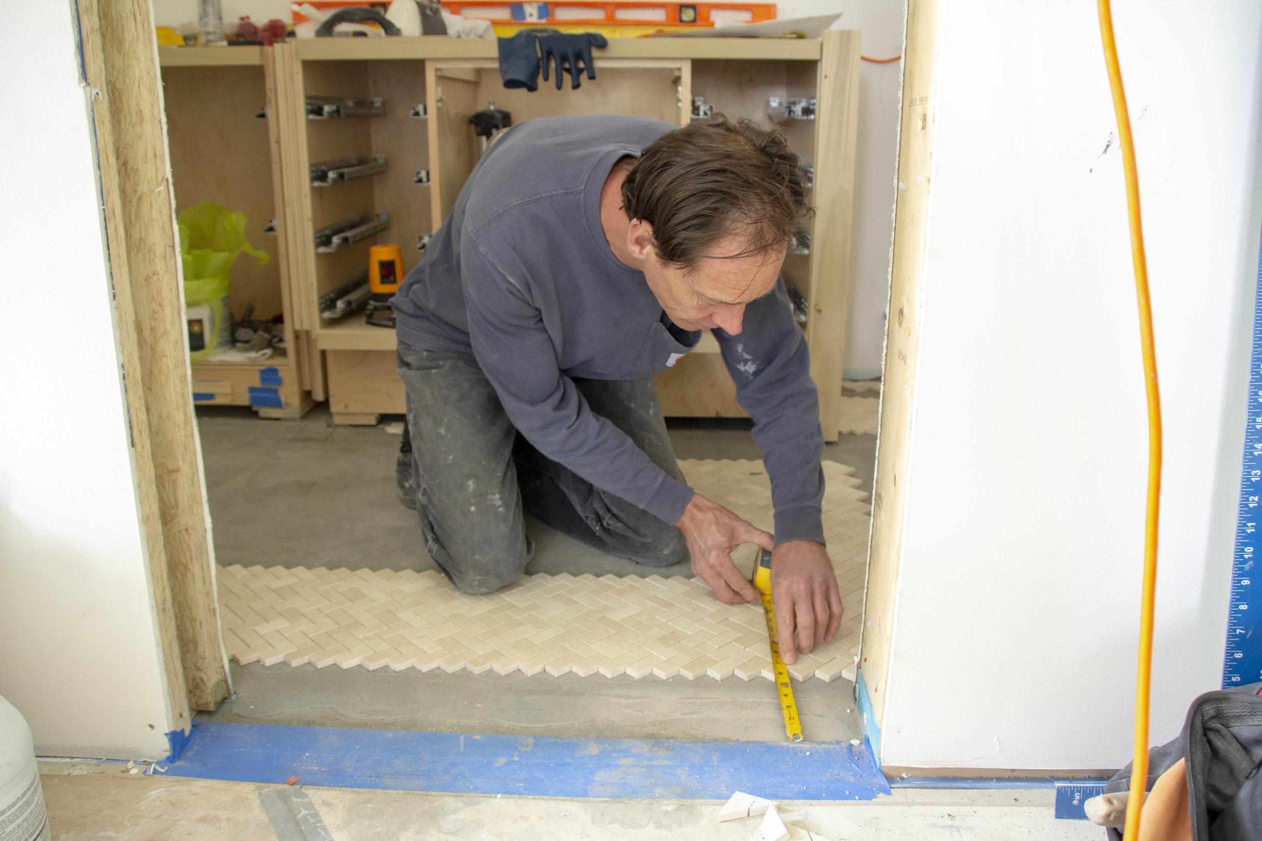 Worker Measuring floor near door.jpg