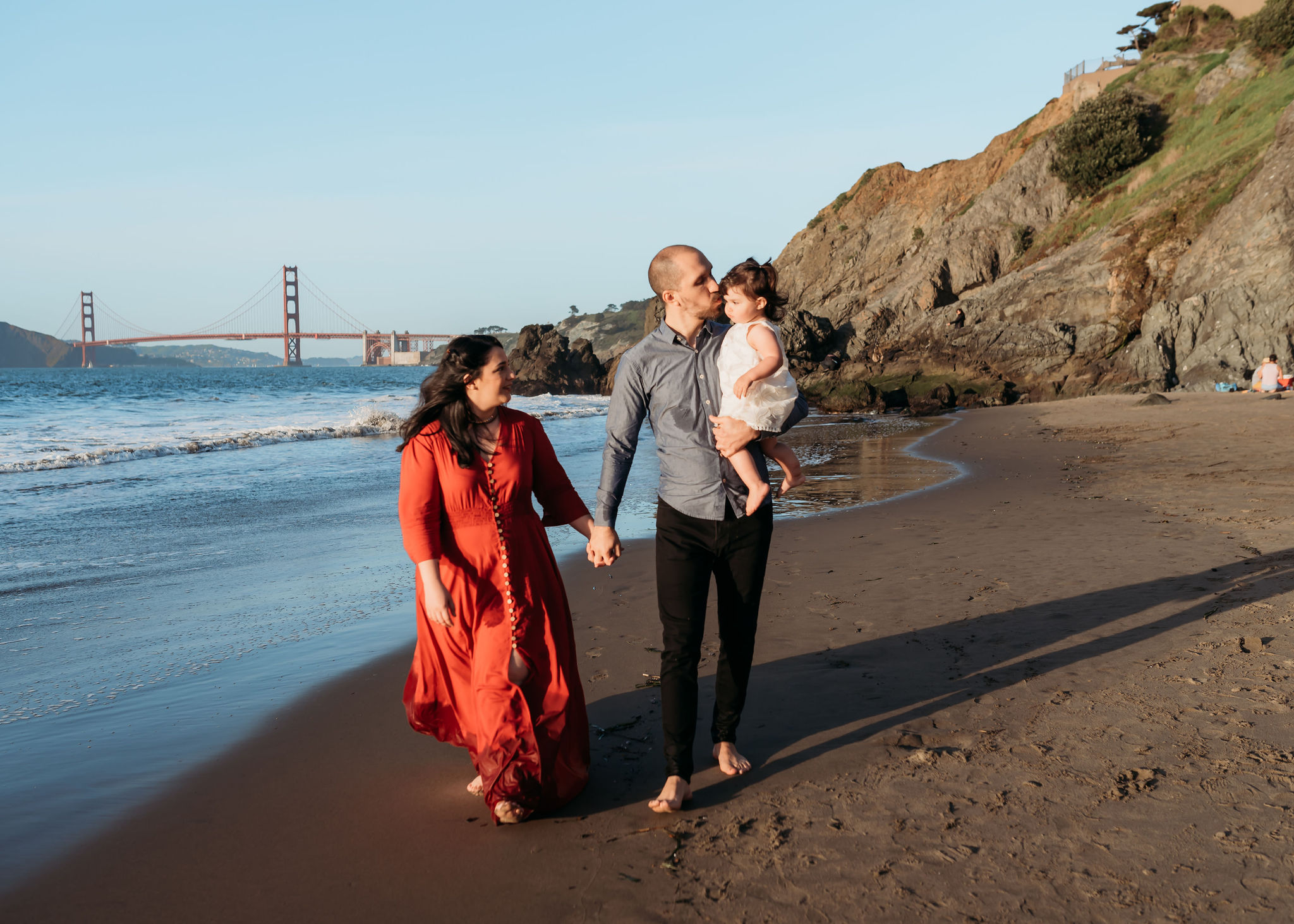 - Another example of how a pop of color can change the entire photo! Dad and Daughter are in very neutral colors while Mom's burnt orange dress contrasts the coastal background and ties in with the Golden Gate Bridge in the background.