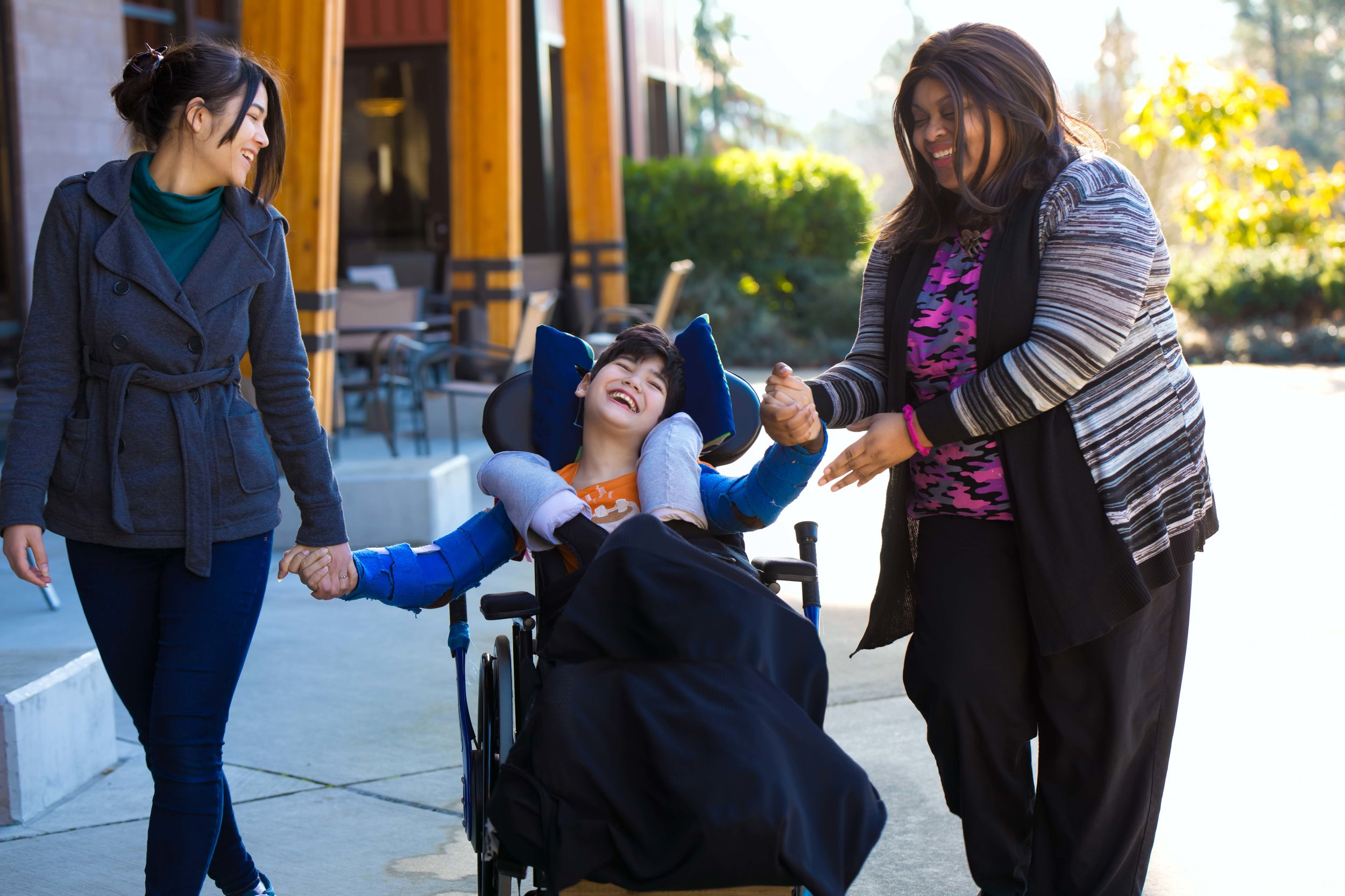 Image of a sunlit streetscape where two women are holding hands with a child in a wheelchair. All three are smiling.