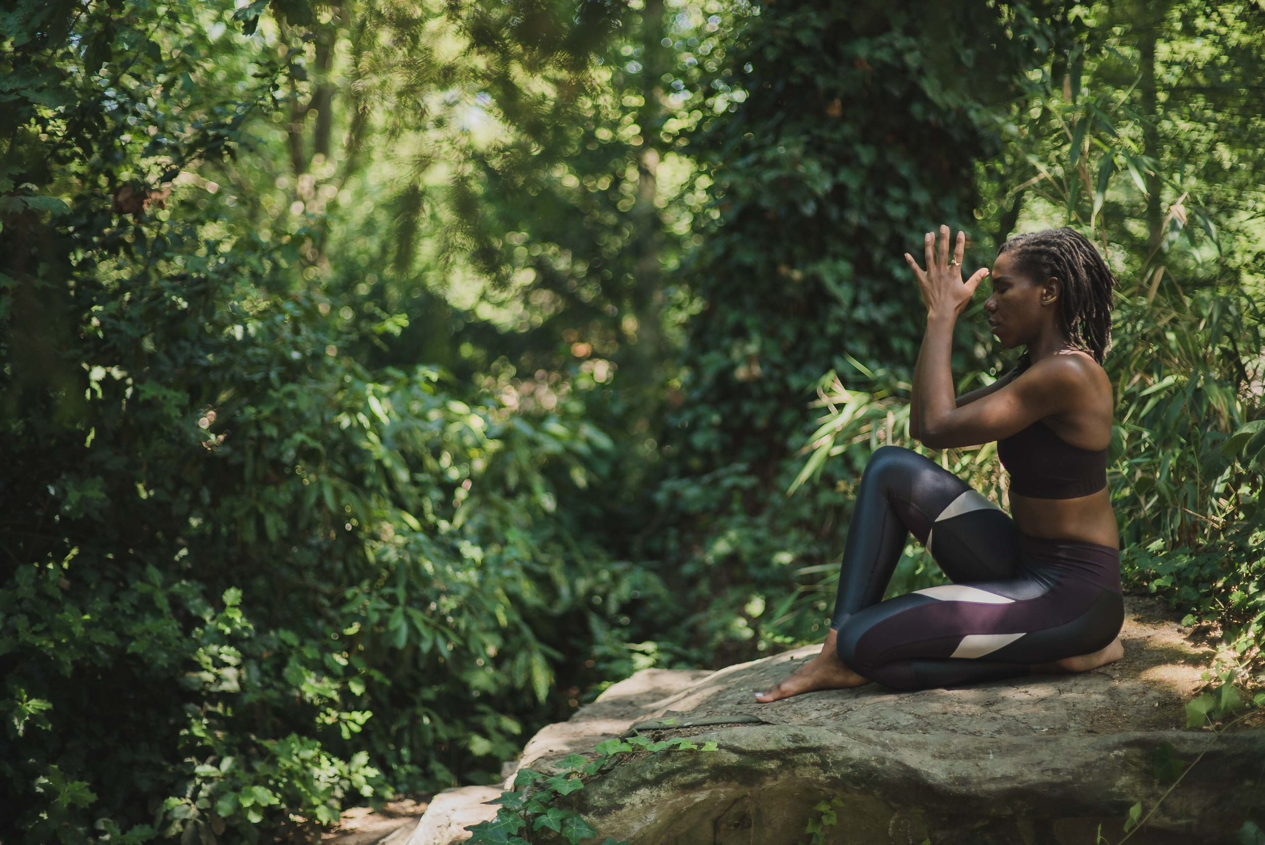 Woman sitting on a stone in a forest and meditating, photo by Jen Armstrong.jpg