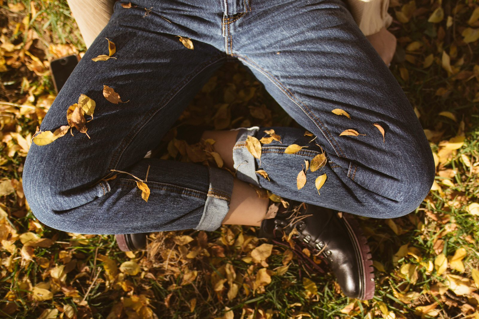 A person meditating with crossed legs, sitting in the yellow leaves on a ground