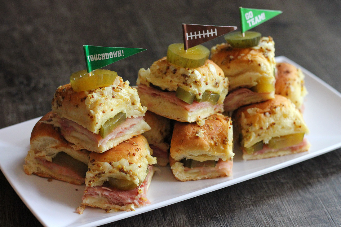 Cubano Sliders - Ingredients1 Tub White Cheddar & Mustard Pickle Dip16 oz Sliced Ham8 Slices Swiss Cheese 12 Dinner Rolls1/4 Cup Butter2 Tbsp Dijon Mustard1/2 tsp Brown SugarDill Pickle Chips for GarnishInstructionsPreheat oven to 350 degrees. Without separating dinner rolls, slice them in half horizontally. Arrange bottoms in a greased 8 x 12 baking pan. Spread a generous layer of pickle dip over the bottom of buns. Top with ham, swiss cheese and a pickle chip.In a microwave, melt butter. Mix in the mustard and brown sugar and stir until smooth and well combined. Drizzle butter mixture  over the top of the rolls. Bake, covered, for 25 minutes. Uncover, bake another 5 minutes until golden brown and heated through.