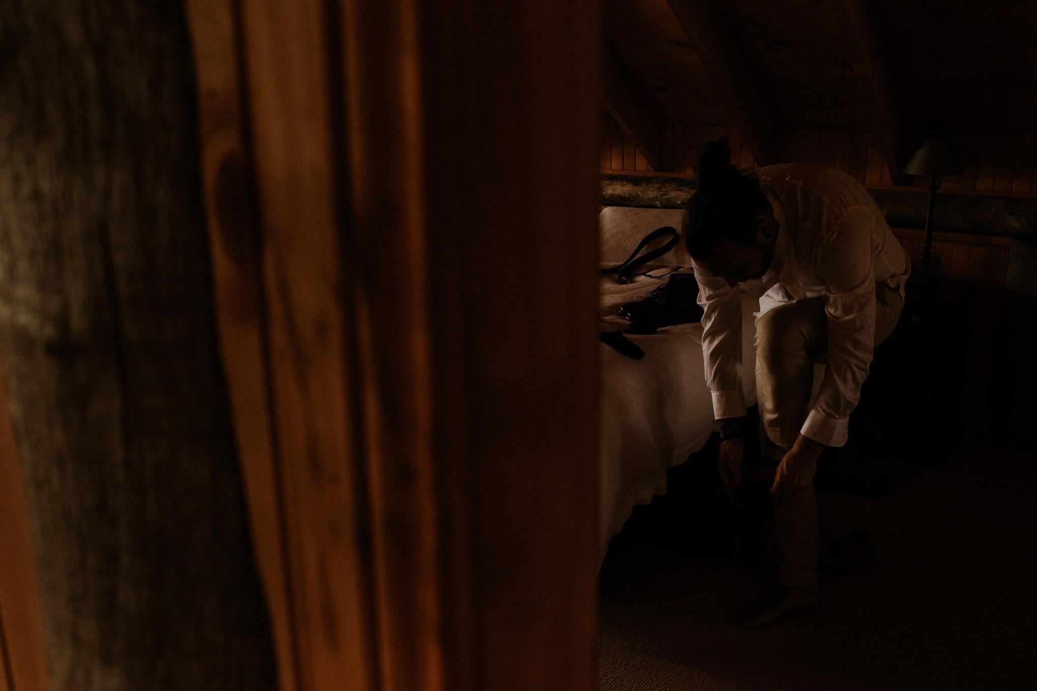 Groom getting ready in rustic timber cabin at Waldara Farm