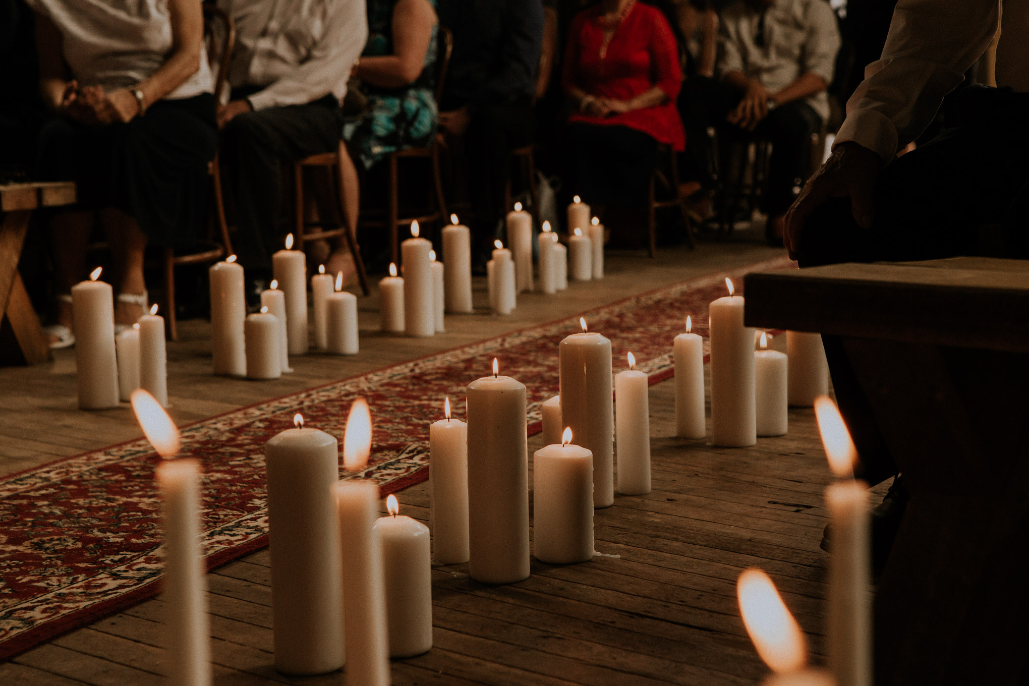 Candles lining the aisle for a wedding in a rustic shearing shed