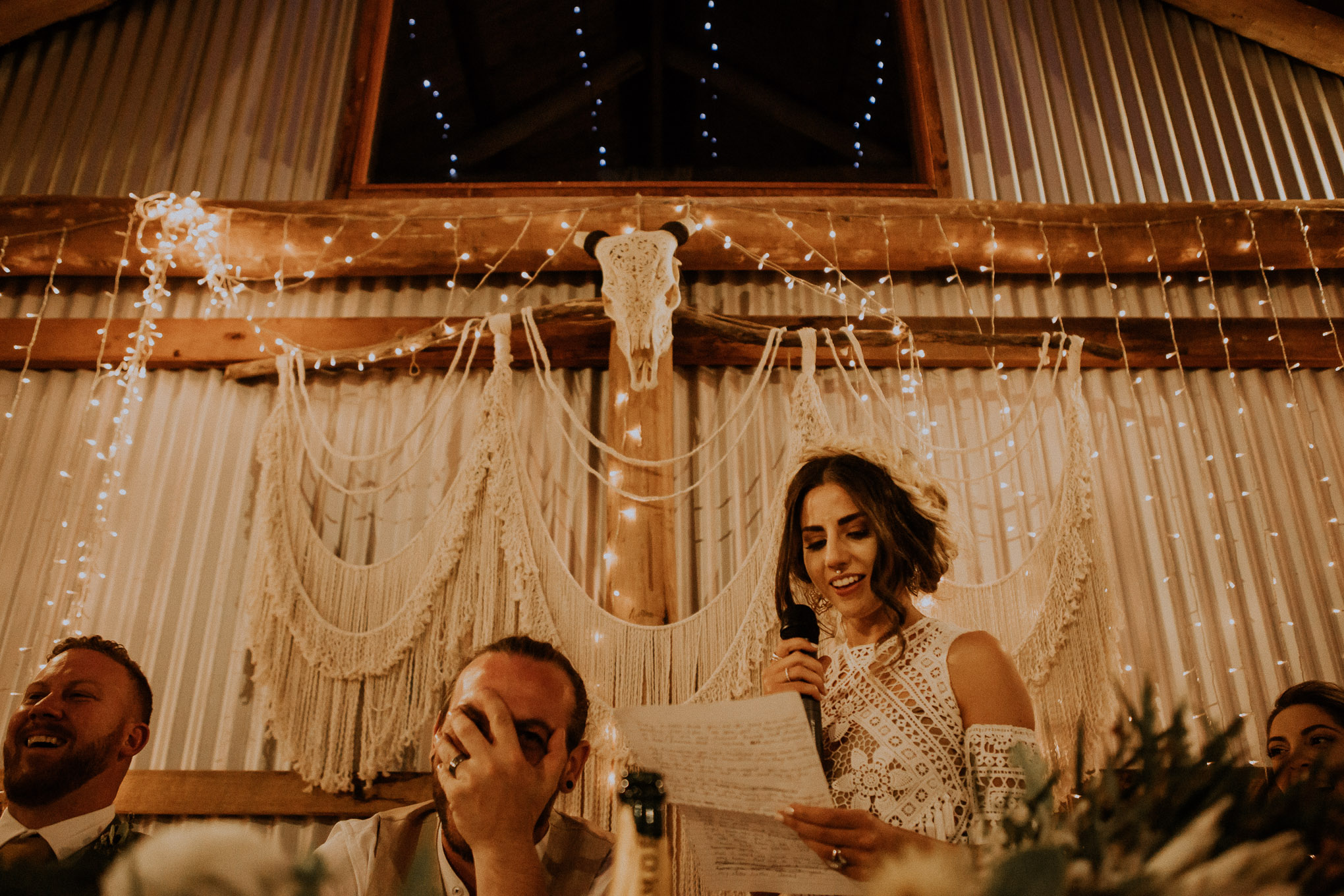 Emotional speeches during a heartfelt wedding ceremony, with fairy lights and macrame