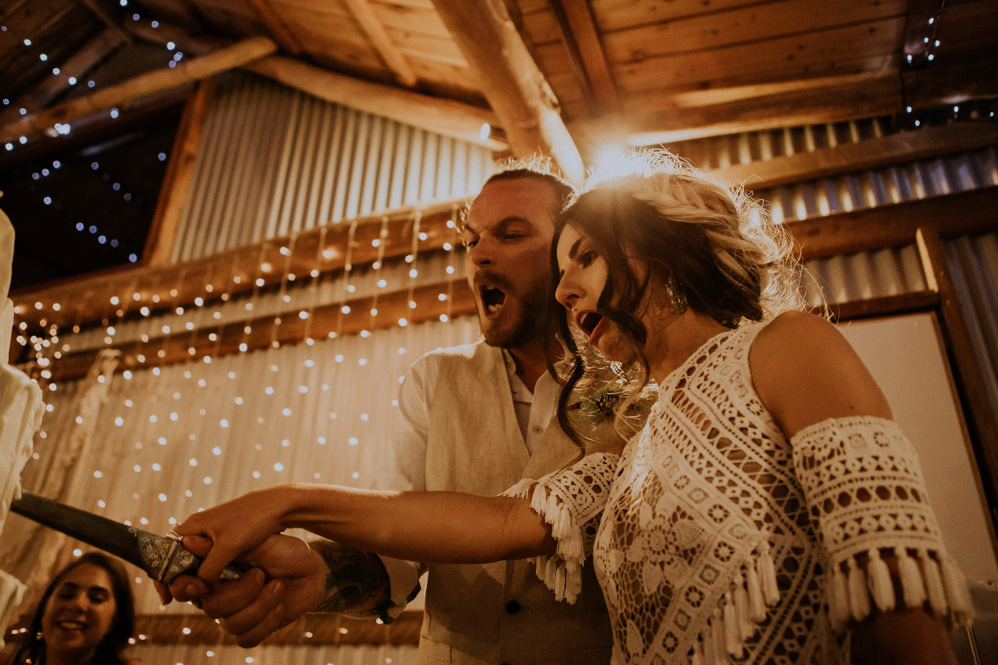 Bride and groom cut their cake during a fairy light-lit wedding reception