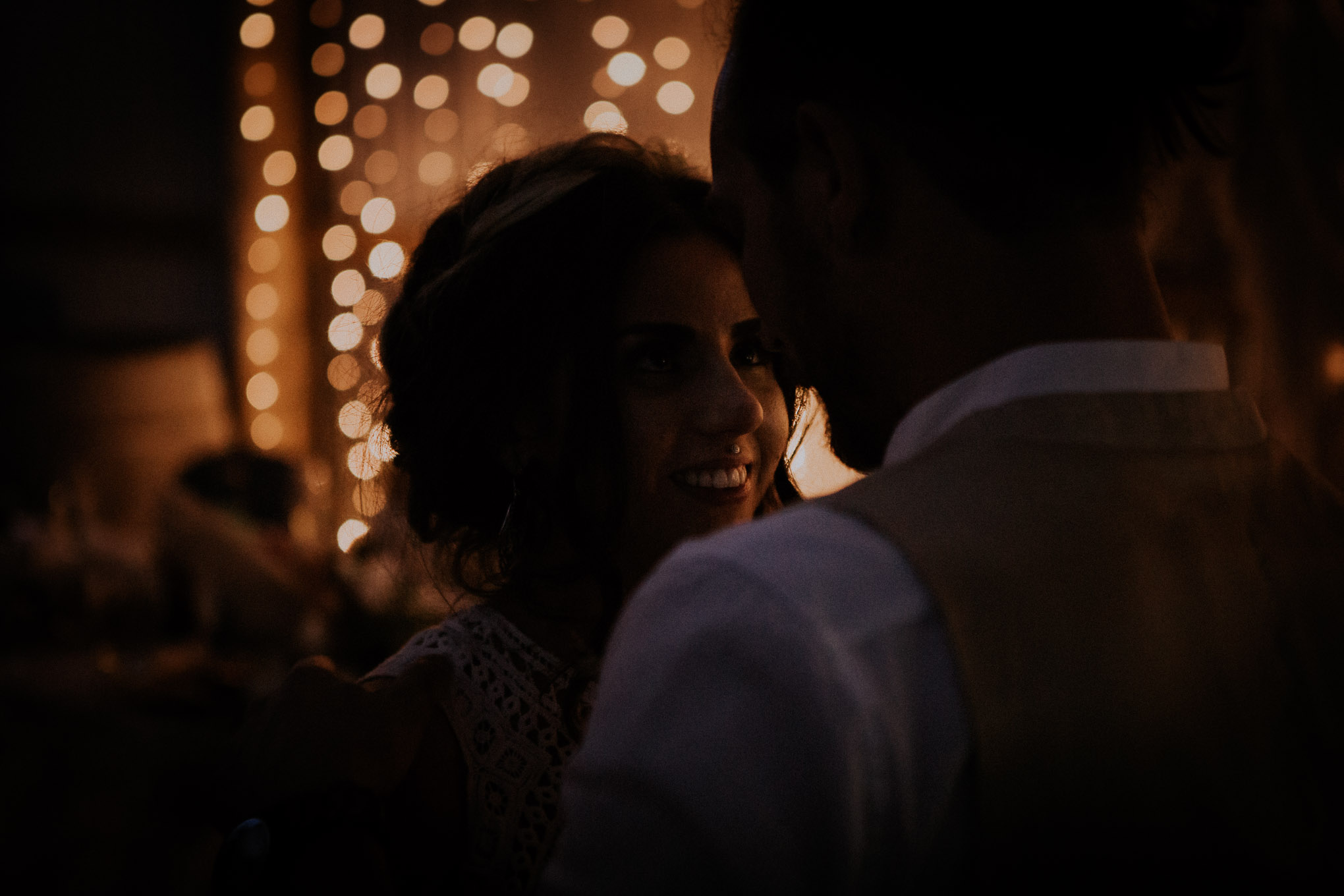 Bride and groom have their first dance during a fairy light-lit wedding reception