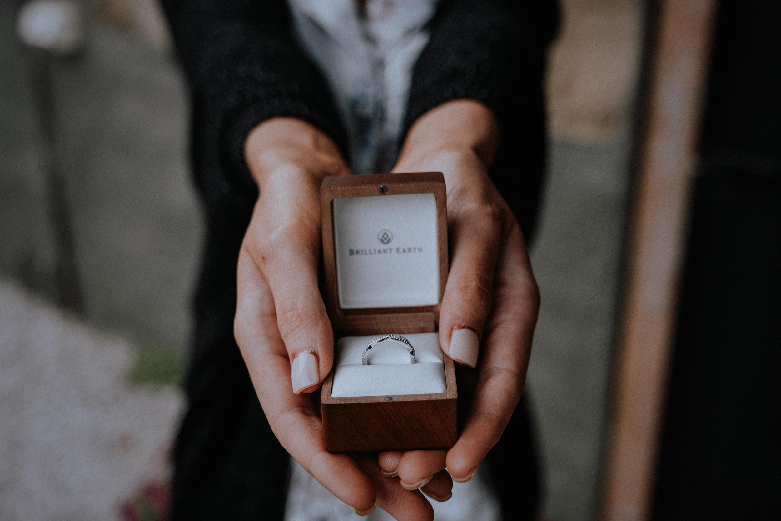 A bride shows off her wedding ring in the box by Brilliant Earth